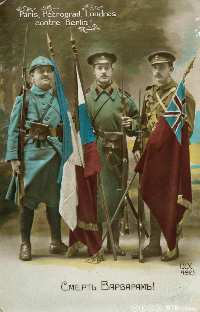 Tre soldater med hvert sitt flagg som symbol på trippelententen: Frankrike, Russland og Storbritannia. Foto av postkort.