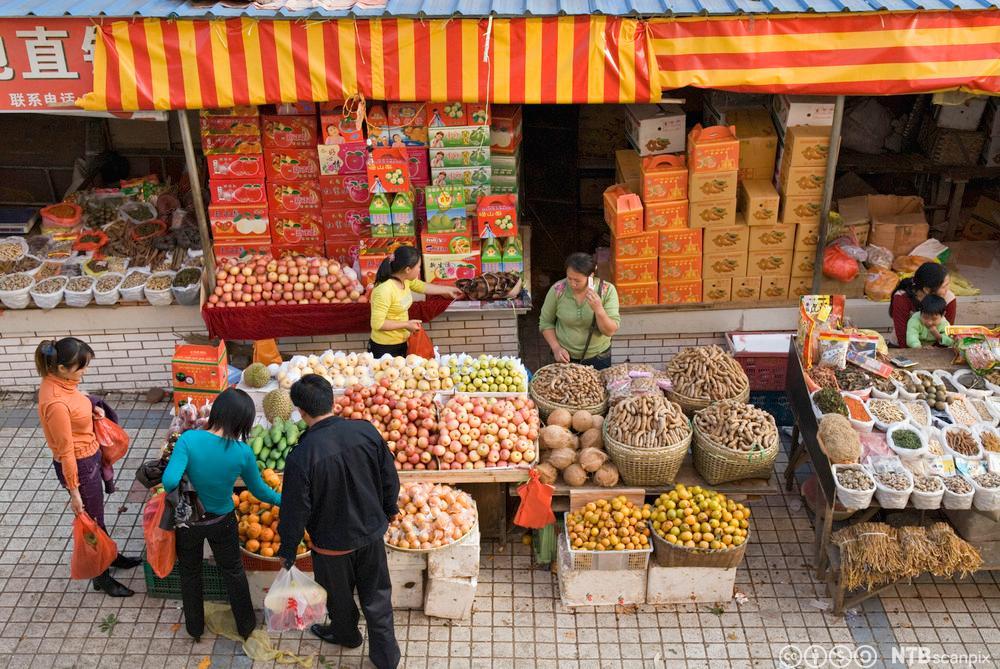 Kunder studerer utvalget i en frukt- og grønnsaksbod i Kina. Foto.