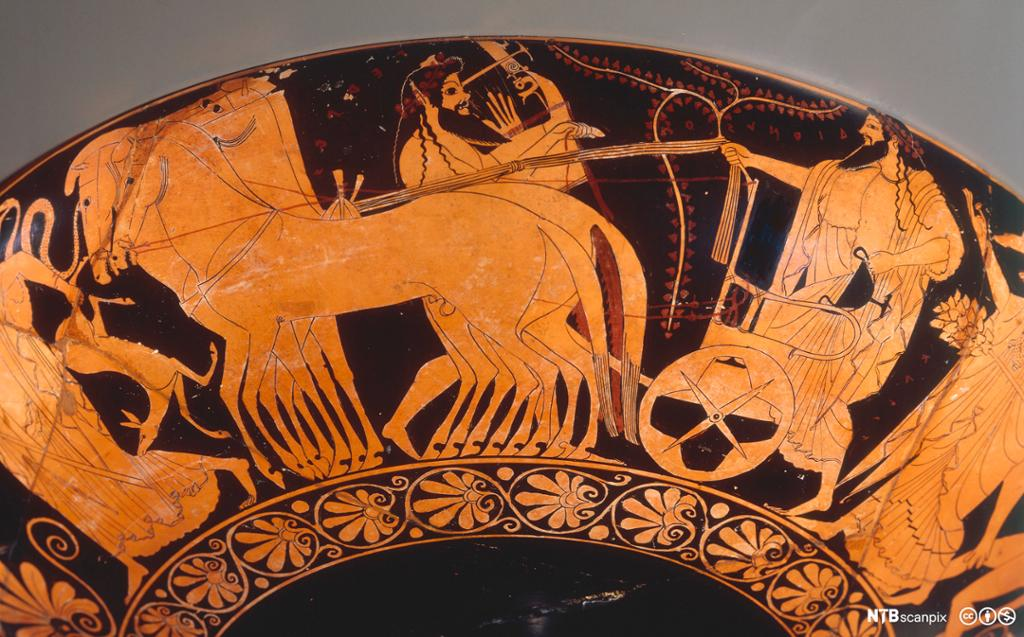 Utsnitt fra vase. Motivet viser menn med langt hår og skjegg, iført hvite kapper og en vogn med hester foran. Foto.