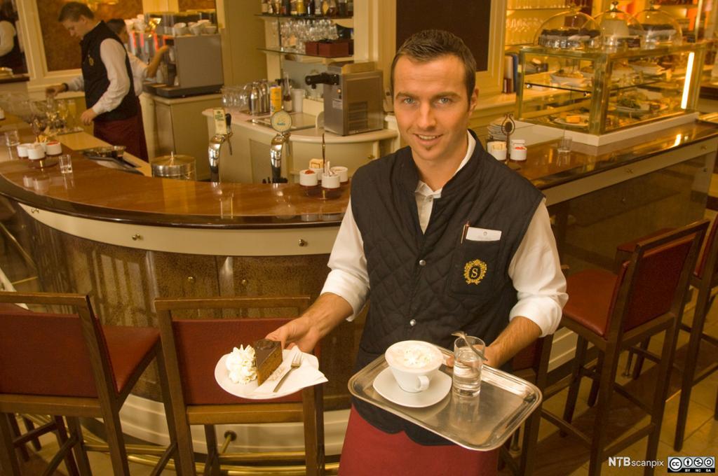 Kelner som bærer på asjett med Sachertorte og et brett med en kopp kaffe og et glass vann. Kafédisk i bakgrunnen. Foto.