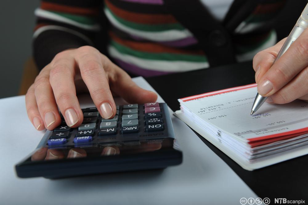 Kvinne med kalkulator. Foto.