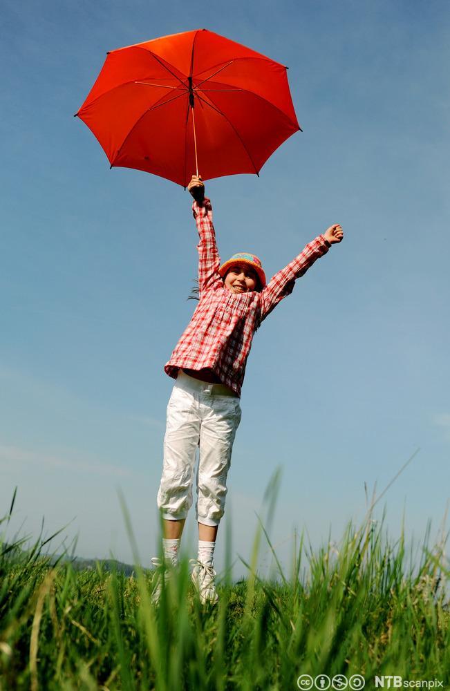 Jente med rød paraply som hopper. Foto.