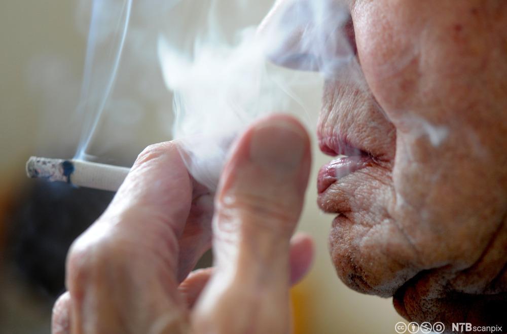 Eldre person røyker en sigarett