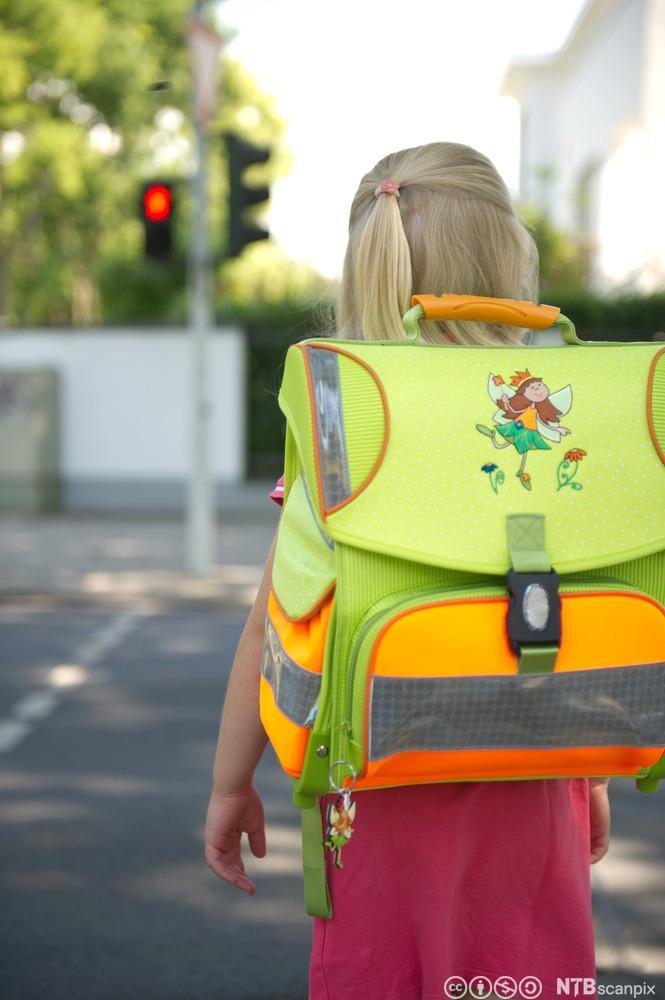 Jente med skolesekk første skoledag. Foto.