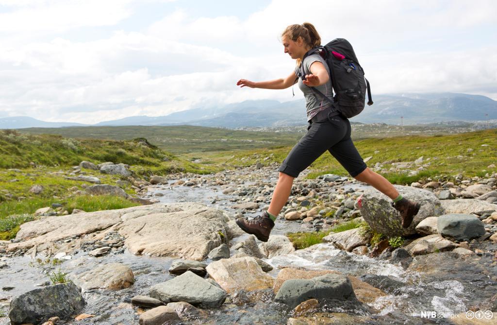 Fjellvandrer med sekk hopper over bekk på tur i fjellet. Foto.