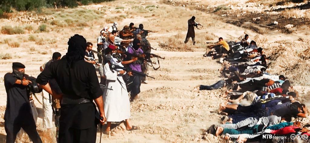 Maskerte personer med automatvåpen sikter på en lang rekke med personer som ligger på magen med hendene over bak hodet. Foto.