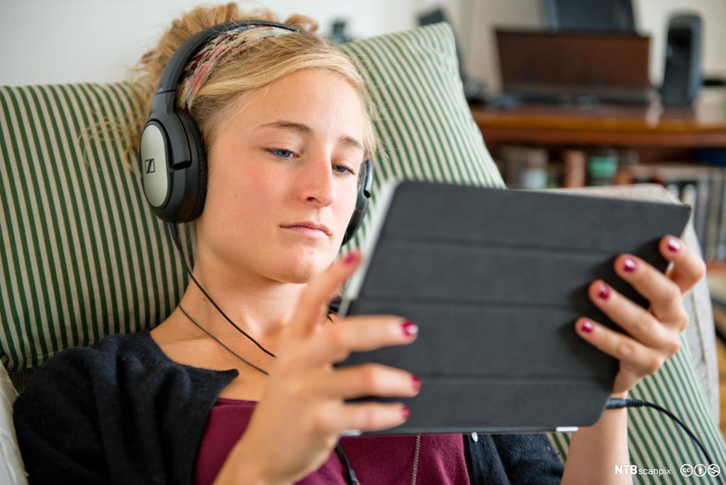 Jente med hodetelefoner og iPad. Foto.
