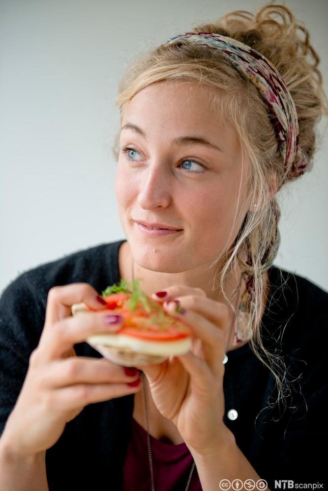 Ung jente som et brødskive med kvitost. Foto.