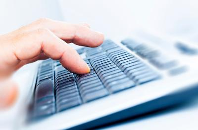 Nærbilete av ein som skriv på tastatur. Foto.