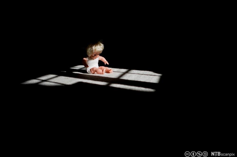 Dukke sitter på gulvet i dramatisk lys. Foto.