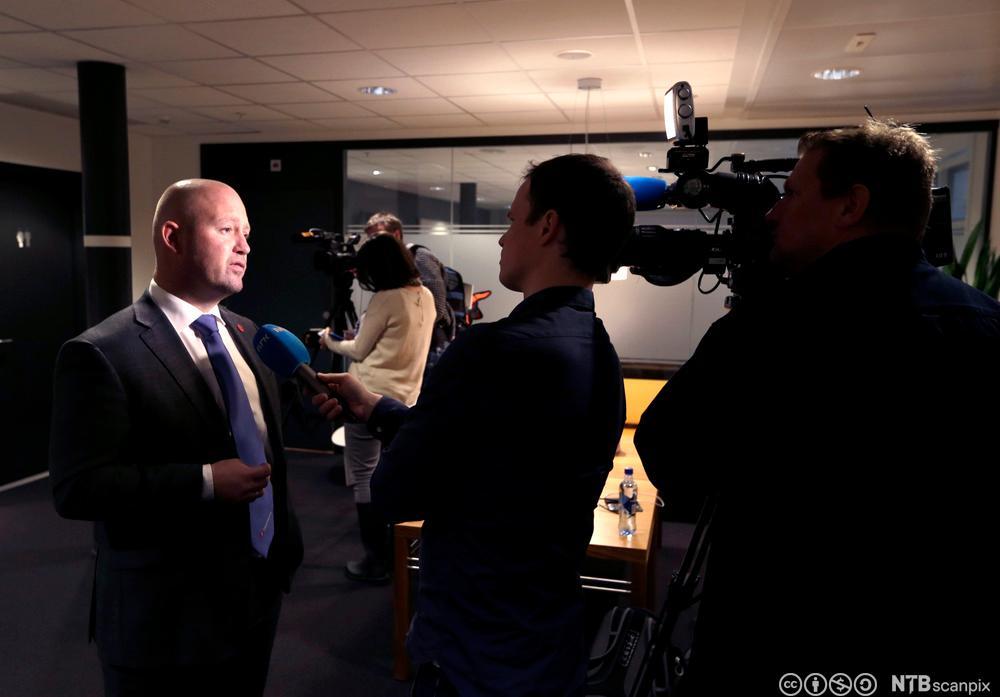 Justisminister Anders Anundsen  blir intervjuet av journalister. Foto.