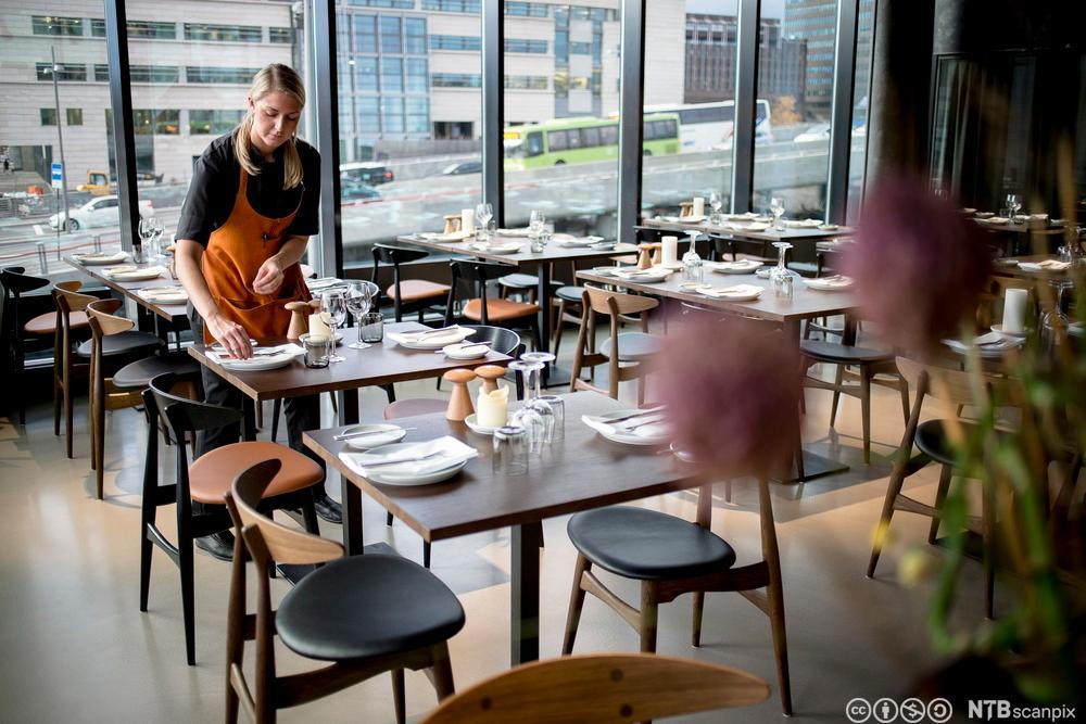 En servitør dekker opp bord i en restaurant. Foto.