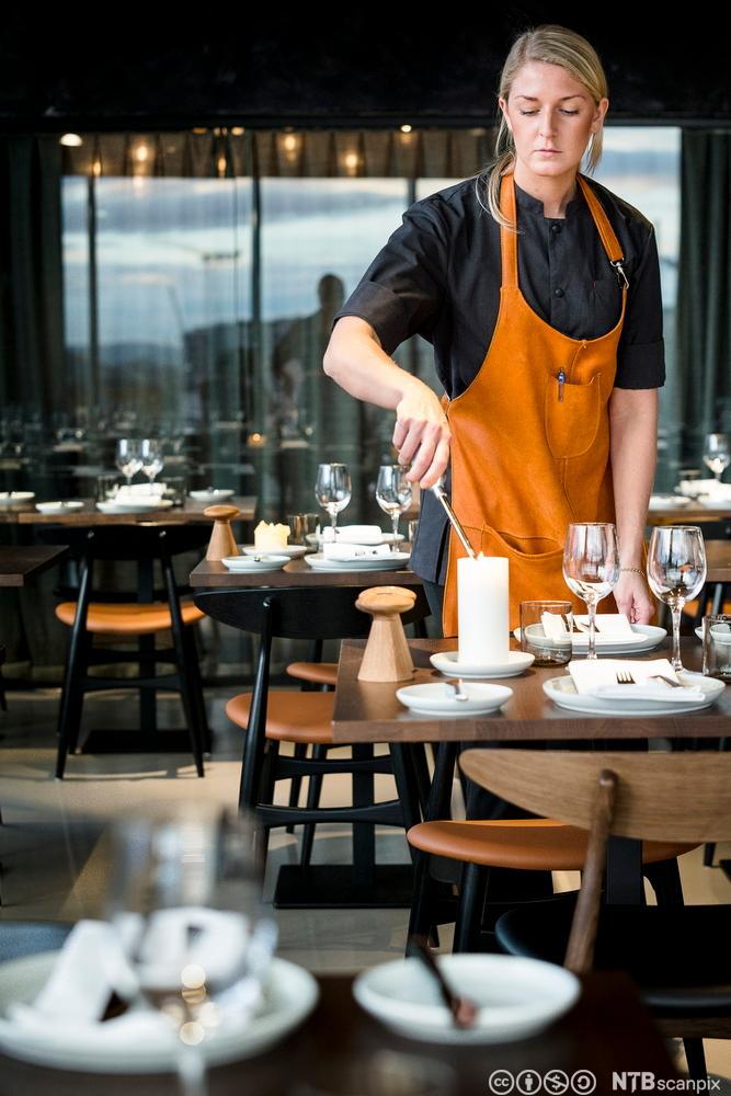 En servitør tenner lys på et bord i en restaurant. Foto.