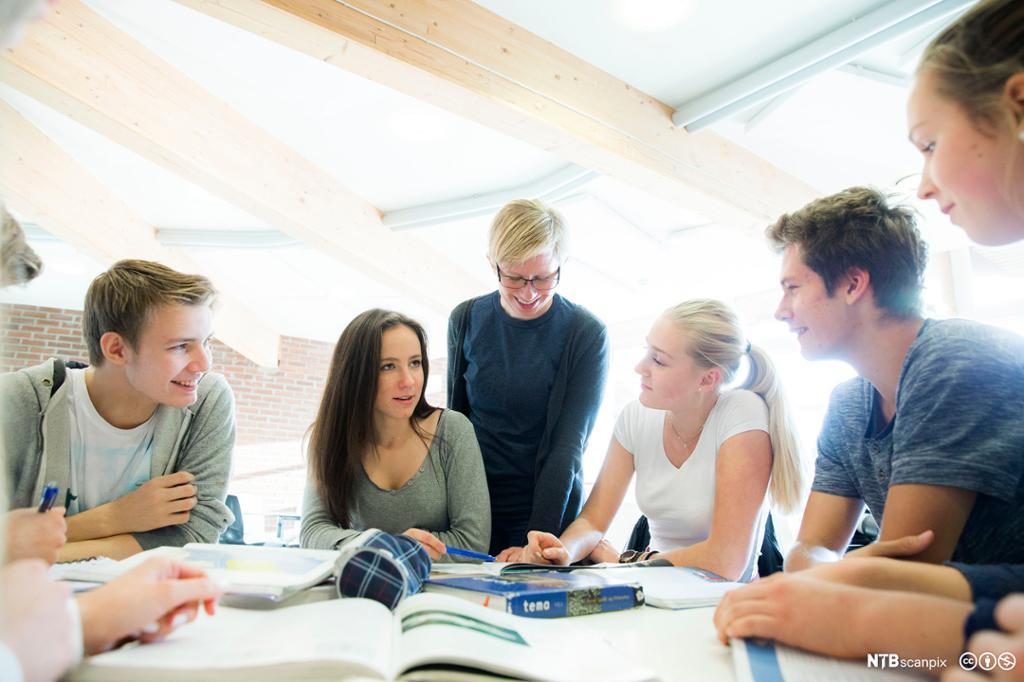 Syv elever som smiler og ser på hverandre sitter rundt et bord med bøker. Foto.