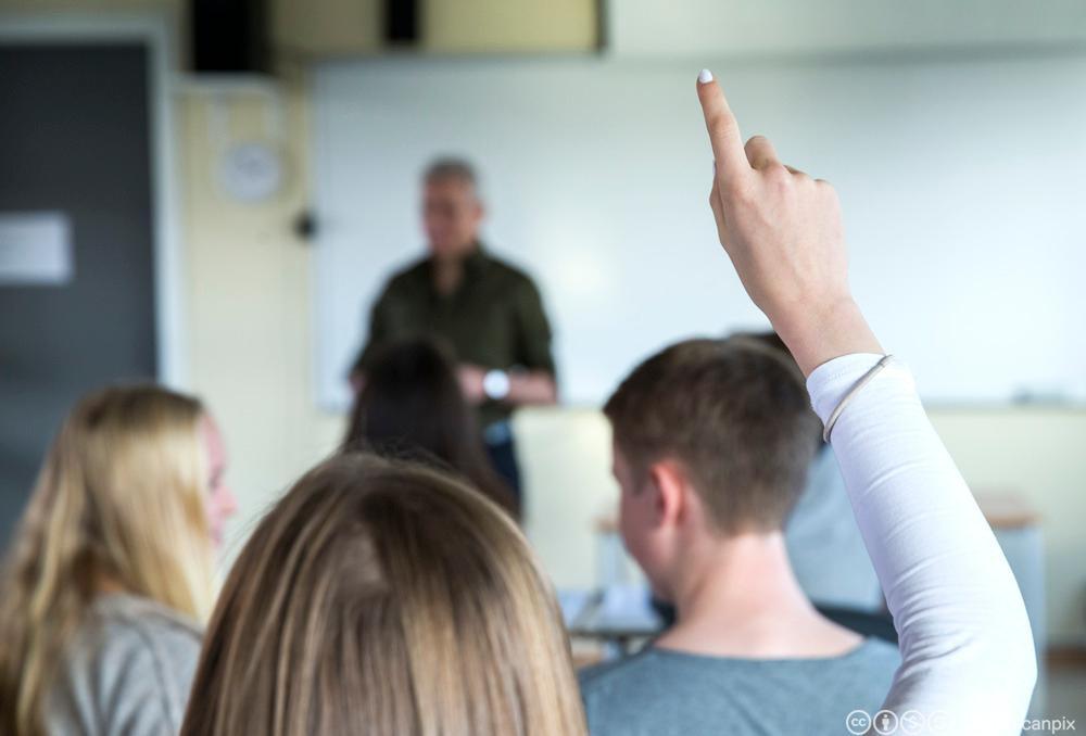 Elev rekker opp hånda. Foto.