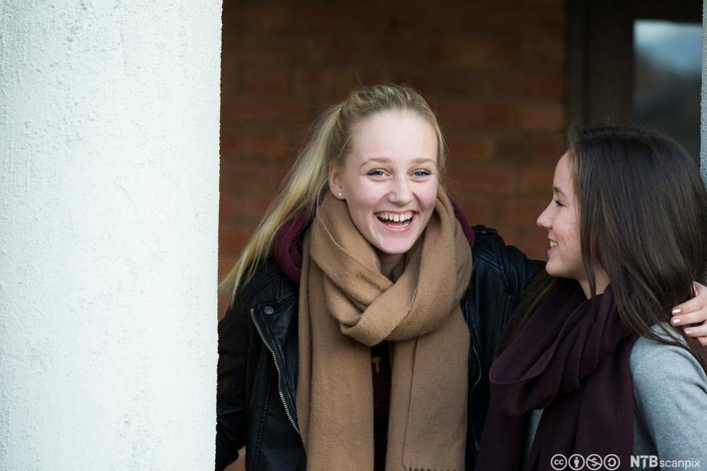 To jenter snakker sammen. Foto.