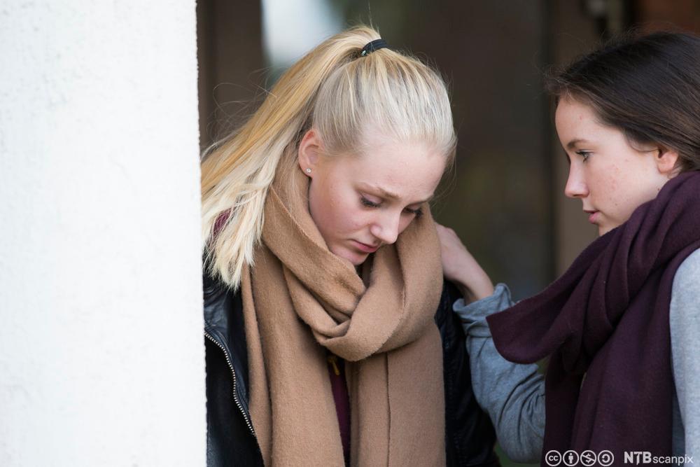 Jente får trøst av venninne. Foto.
