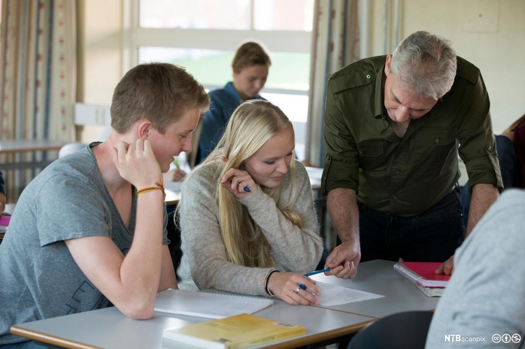 Lærer veileder to elever i klasserommet.foto.