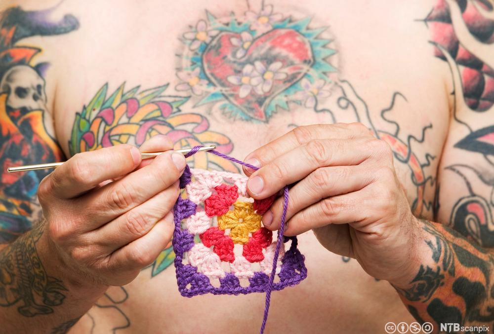 Mann med tatovering hekler. Foto.
