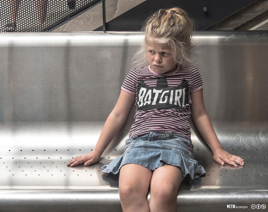 Sur jentunge på moderne benk. Bilde.