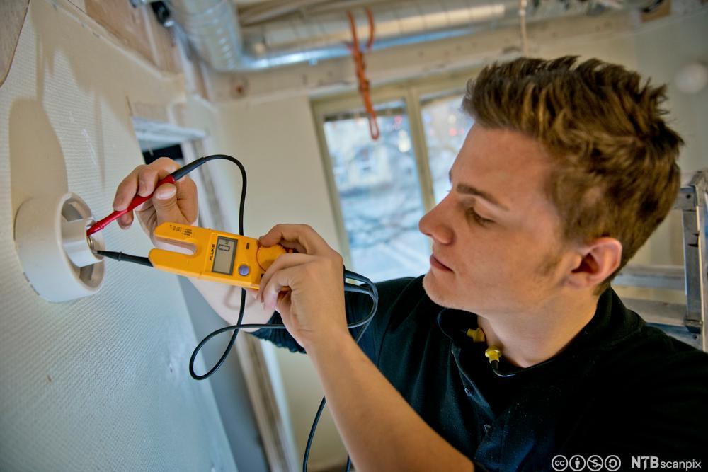 Elektriker måler elektrisitet i en vegglampe. Foto.