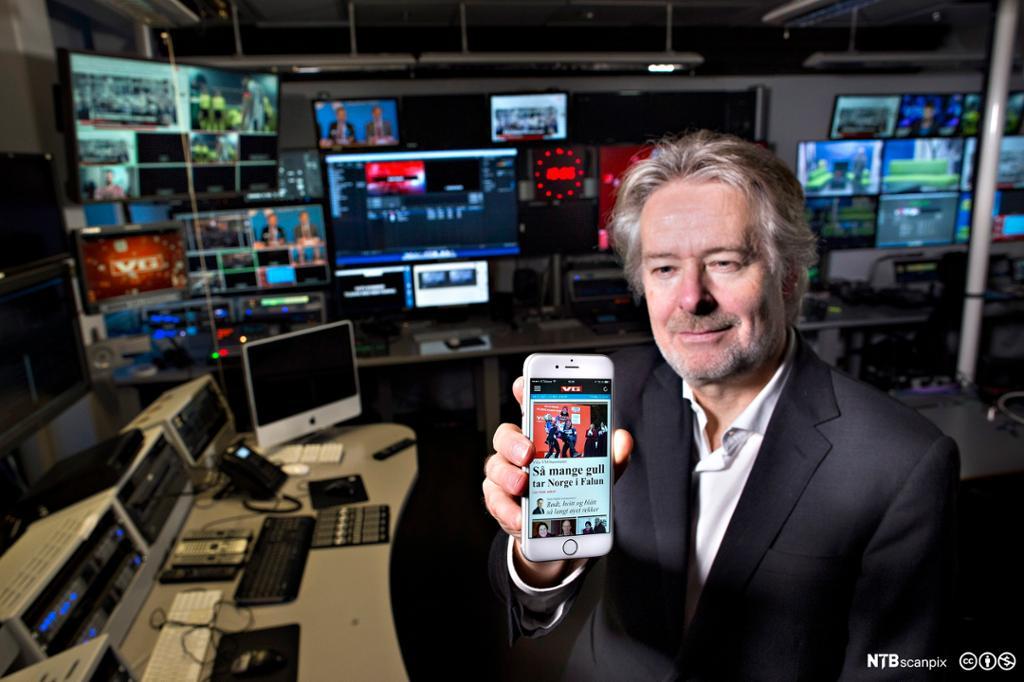 Redaktør Torry Pedersn holder opp en mobil med VGs nettsider i VGs fjernsynsstudio. Fotografi.