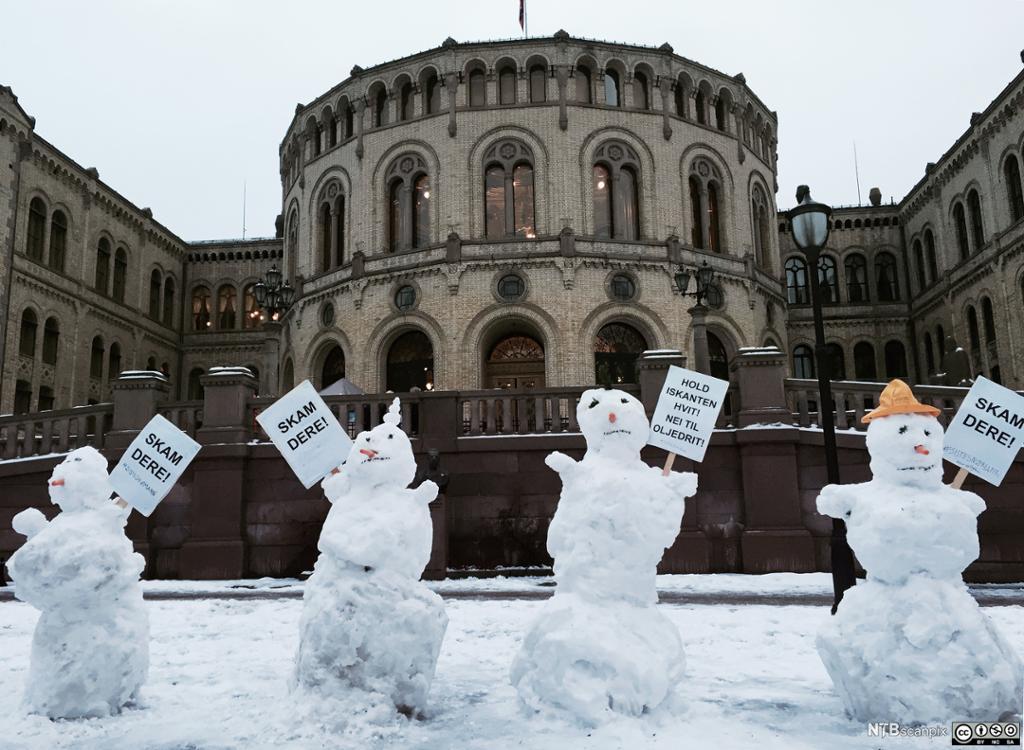 Snømenn protesterer med plakater foran Stortinget. Foto.