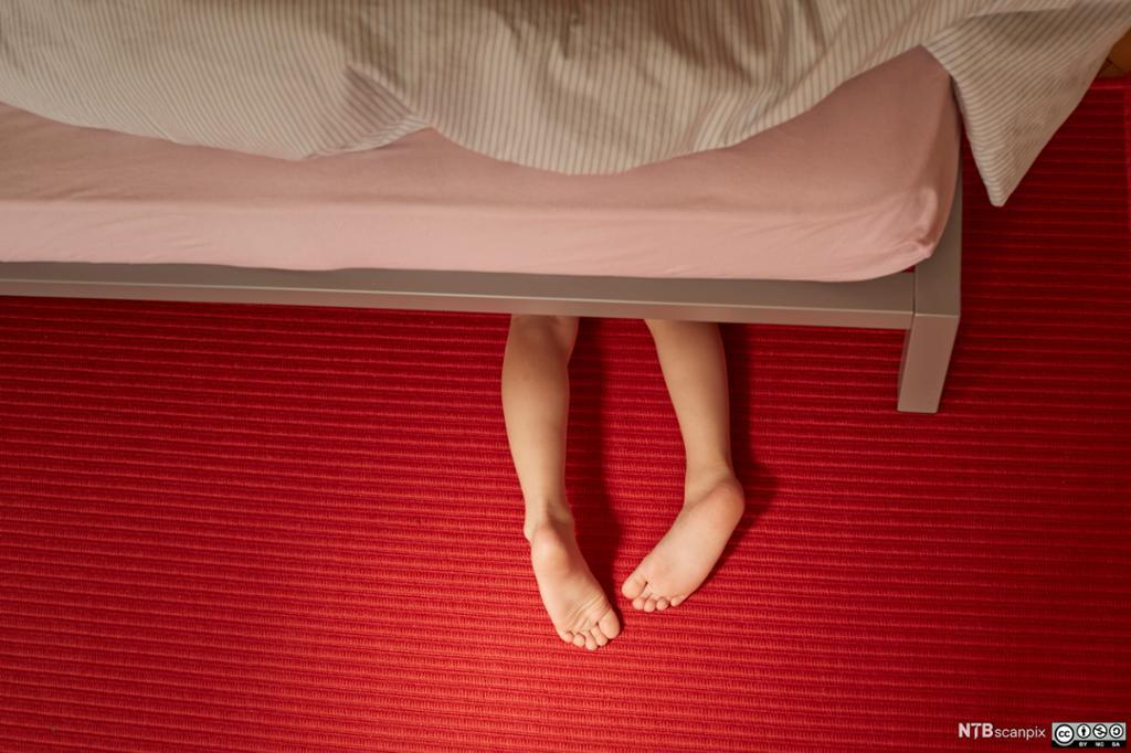 Et barn ligger under senga. Foto.