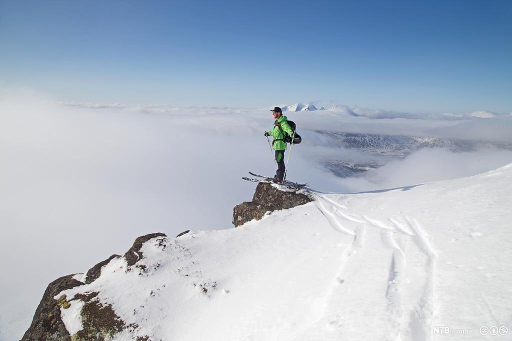En mann nyter tsikten fra en fjelltopp i Lofoten. Foto.