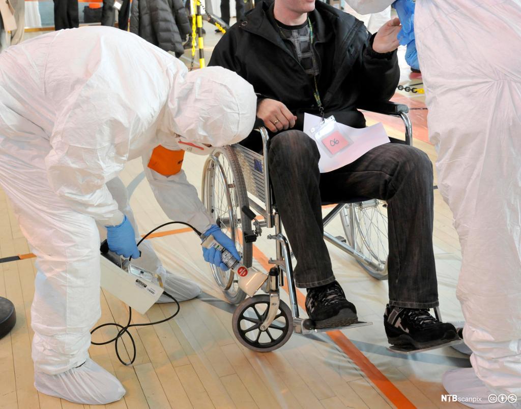 Person i hvit vernedrakt måler stråling fra rullestol. Foto.