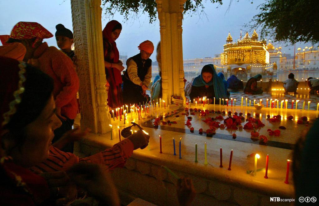 Kvinner tenner mange små stearinlys på en opphøyd firkant. I bakgrunnen et tempel. Foto.