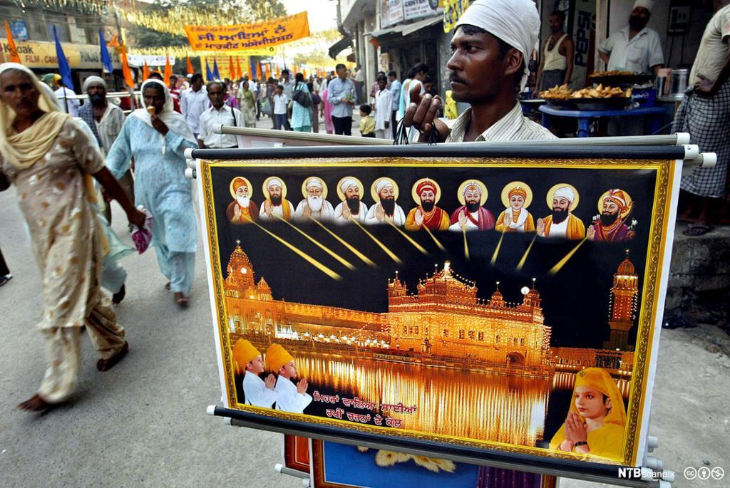 Mann bærer bilde av ti guruer og et gyldent tempel i prosesjon. Foto.