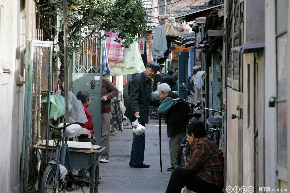 En eldre kinesisk mann hilser på en eldre kinesisk dame i en av Beijings mange tradisjonelle bakgater. Foto.