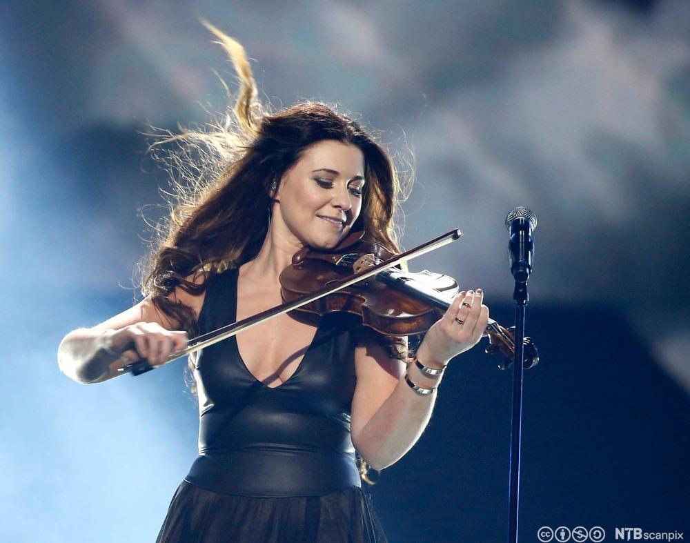 En ung kvinne spiller fiolin på en scene. Foto.