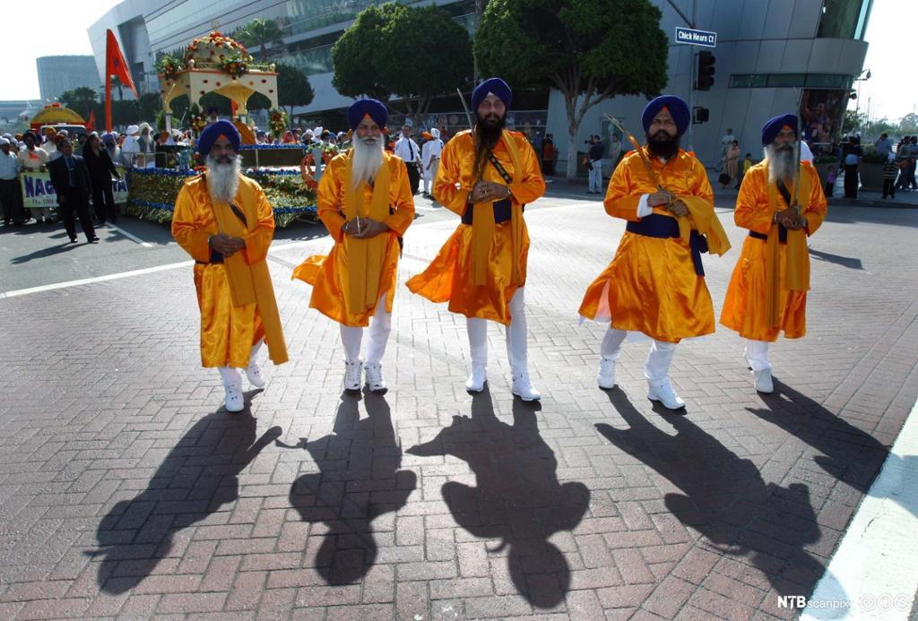 Fem menn med sverd i orange klær og blå turban går først i en parade. Foto.