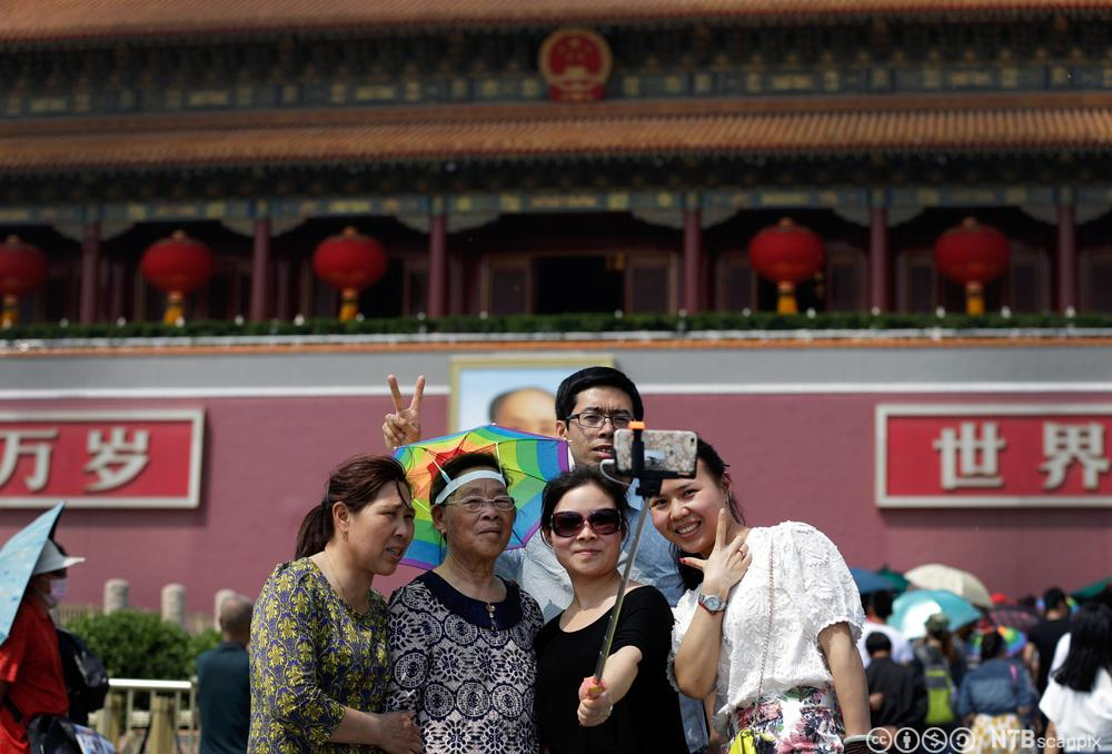 En kinesisk familie tar gruppeselfie utenfor Den forbudte by på Tiananmen-plassen. Foto.