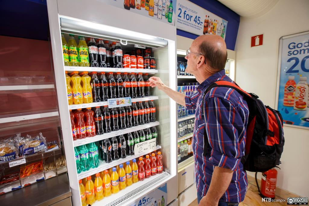 En eldre mann står med utstrakt hånd og skal velge seg en drikkeflaske fra en kjølehyle i en butikk. Foto.