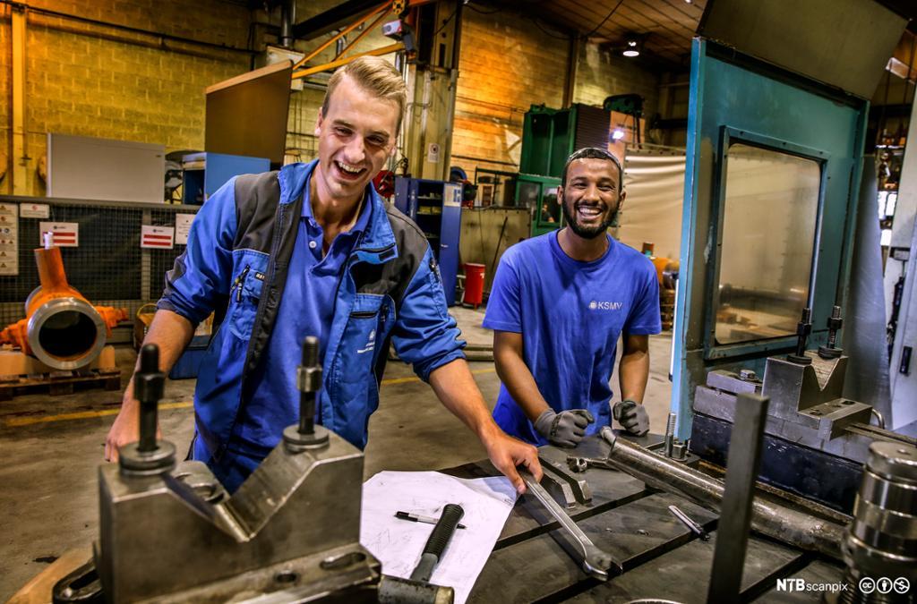 To lærlinger på et mekanisk verksted. De står ved arbeidsbenken og smiler bredt. Foto.