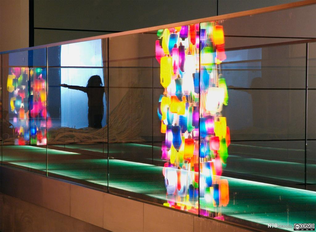 Refleksjoner av fargede flasker og jente i speil. Foto.