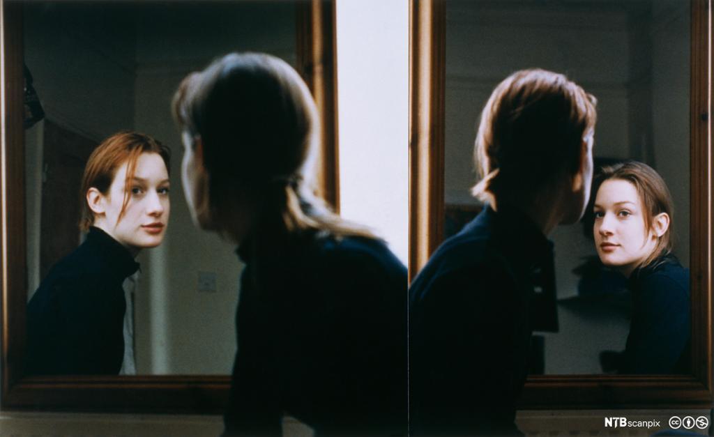 Tvillinger som ser seg selv i speilet. Foto.