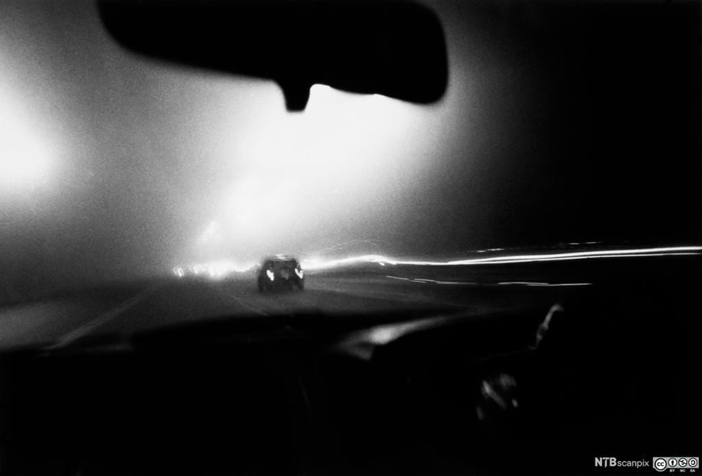 En bil som kjører på en vei om natta sett en møtende bil. Foto.