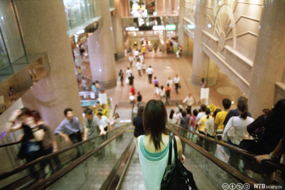 Ung kvinne i rulletrapp i kjøpesenter. Foto.