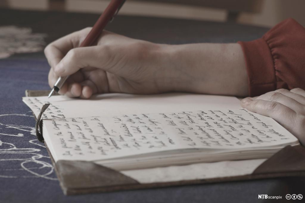 Kvinnehånd som skriver i en bok. Foto.
