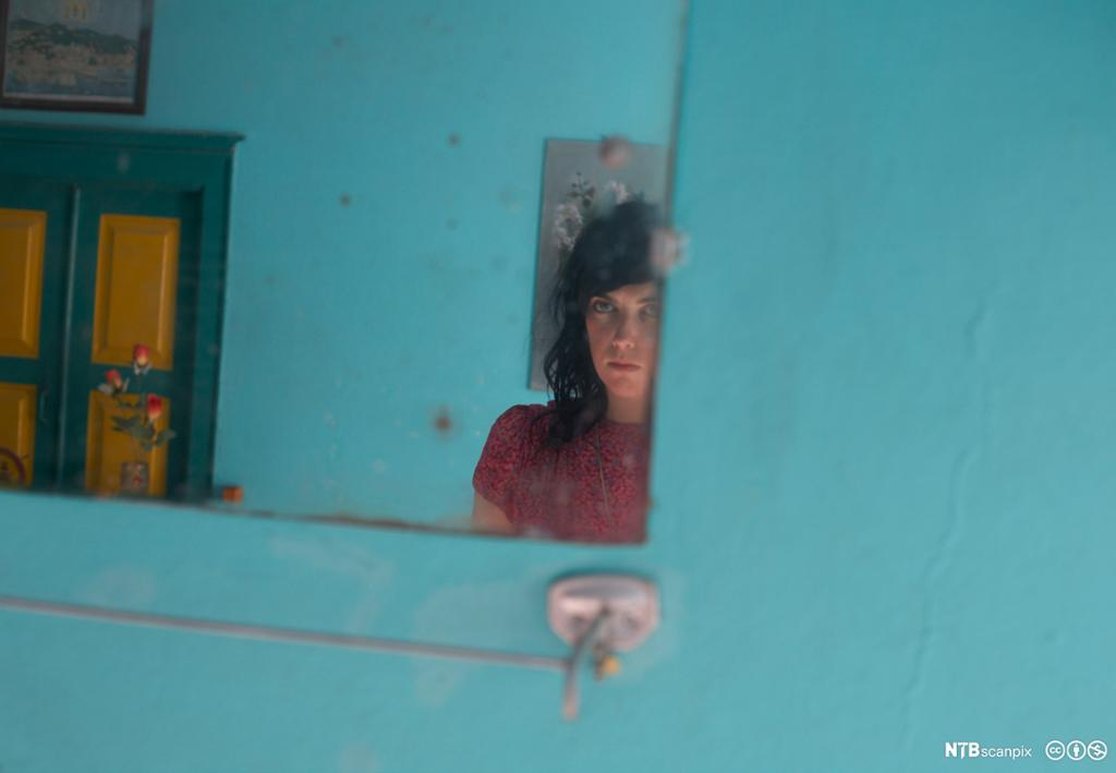 Speilbilde av ung kvinne i blått rom. Foto.