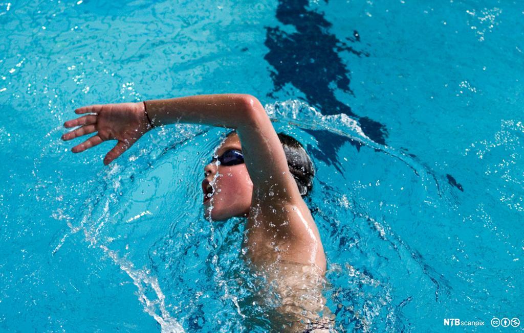 Gutt som svømmer i basseng. Foto.