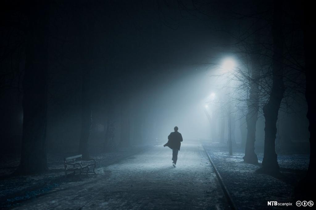Mann som løper om natten, i lyset fra en gatelykt. Foto.