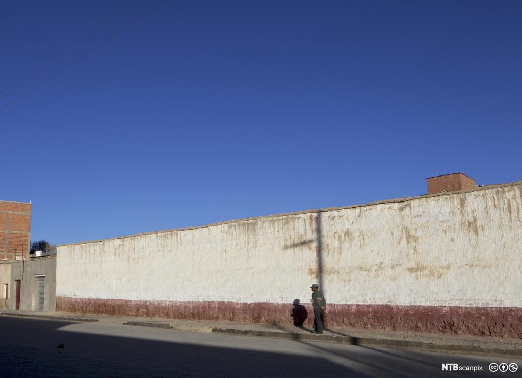 Mann med hund untenfor fengselsmur. Foto.