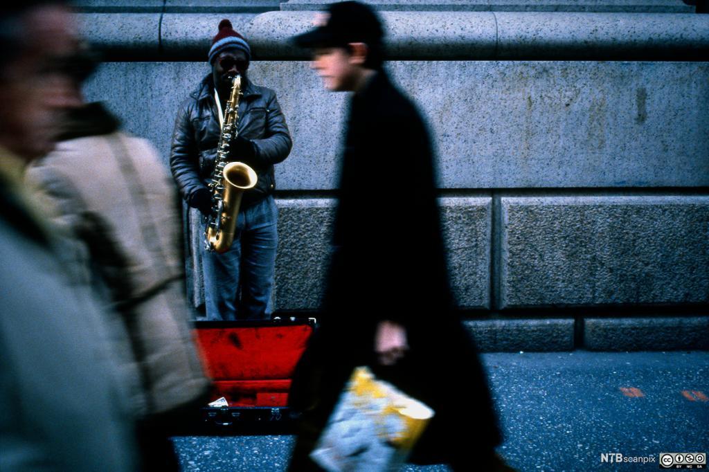 Gatemusikant spiller på en saksofon. Foto.