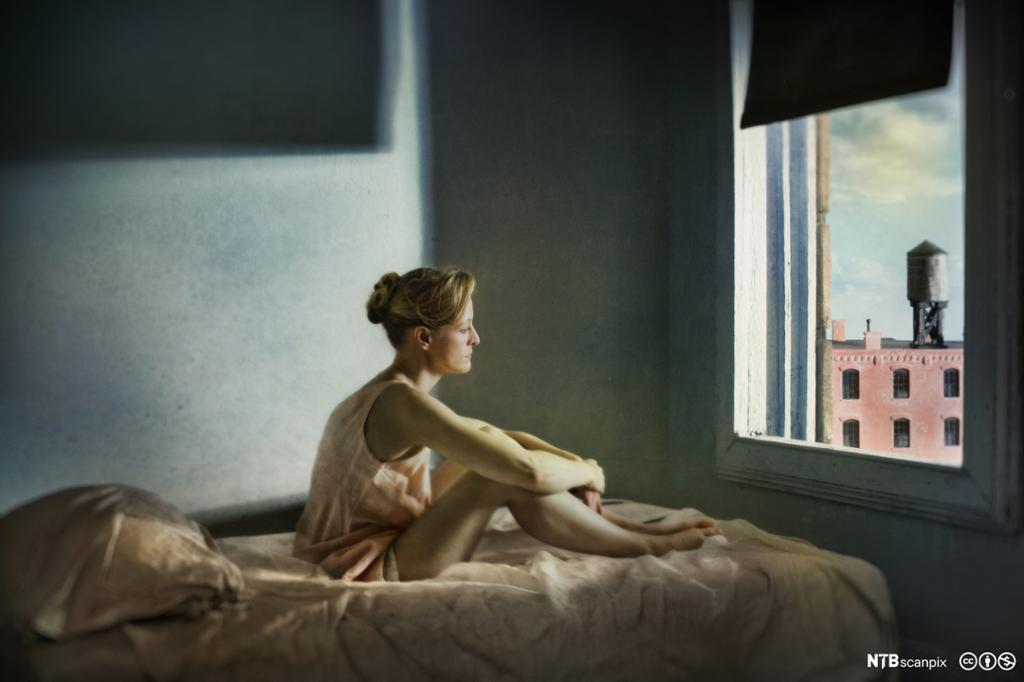 En kvinne sitter på en seng og stirrer tankefullt ut av vinduet på en bygning. Foto.
