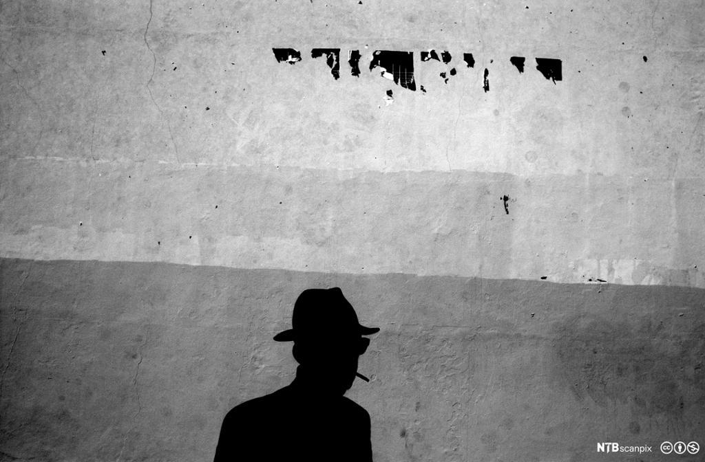 skygge av mann med hatt som røyker. Foto.